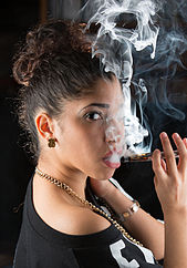 Woman vaping an e-cigarette.