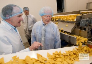 Dinny, pictured agreeing a huge grant for a Gaoth Dobhair crisp factory. It has now closed