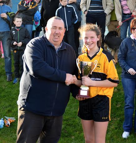 St Eunan's captain Katherine Kelly collects the A Championship U13 title from Dermott Foy today