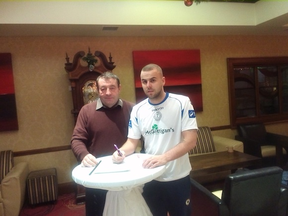 Damien McNulty puts pen to paper with Harps John Campbell.