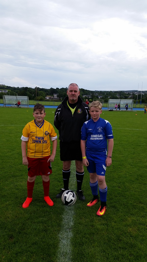 Captains Ethan Deery and Cahir Brady Devenny with match referee John Coyle.