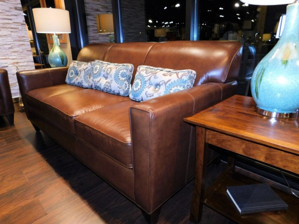 Essentially Yours Sofa with Angle Arm and Dark Trap Legs Shown in Revelation Tobacco Leather Pillows in Gr. 19 #2663 Voyager Cobblestone Partially Customizable. Please contact us for pricing details.