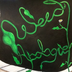 """""""Weed Apologue"""" written in the font of a vine growing from a crack in the sidewalk."""