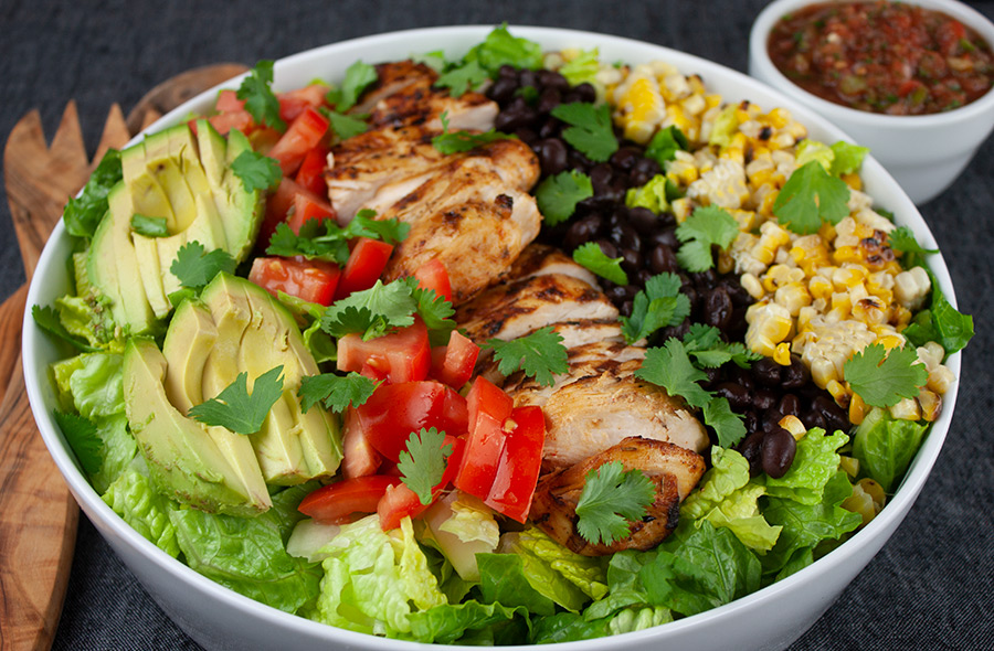 Southwest Grilled Chicken Salad in a large white serving platter with wooden spoons and a ramekin of salsa