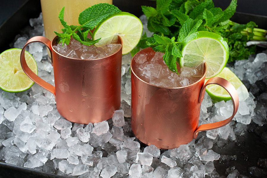 Skinny Moscow Mule - two copper mugs filled with cocktail on a tray of ice garnished with a lime slice and fresh mint leaves