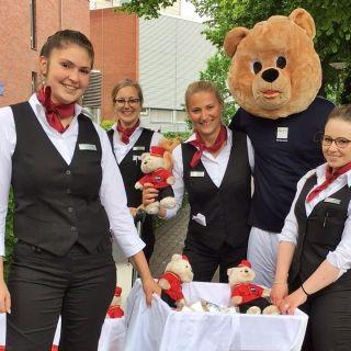 Der Dori Bär zusammen mit Mitarbeiterinnen des Dorint Hotel Hamburg-Eppendorf vor dem Universitätsklinikum Hamburg-Eppendorf schenkt den Passanten zum Weltfreundlichkeitstag ein Lächeln