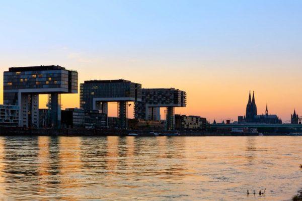 Blick auf die Kölner Kranhäuser, den Rhein und den Dom bei Sonnenuntergang, © iStock