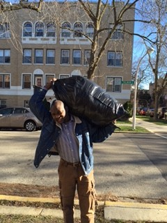 Secretary Abdulatif Isaac in Chicago on Dec., 19, 2015, carrying clothing to newly arrived Darfuri families.