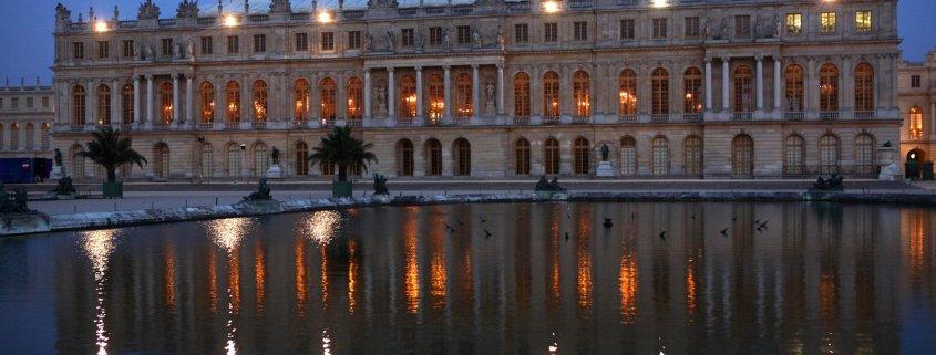 De achterkant van het kasteel van Versailles in Frankrijk bij nacht