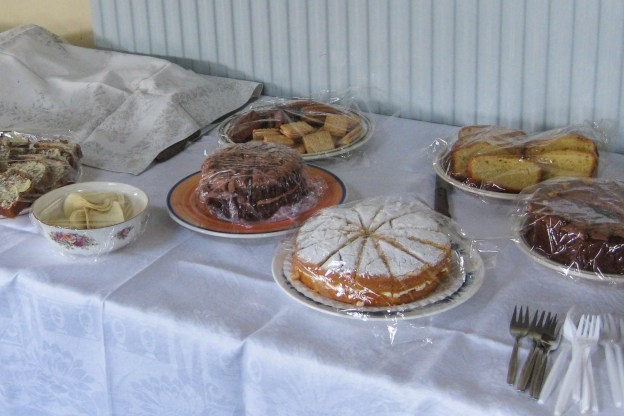 Table with white cloth and selection of cakes covered in cling film