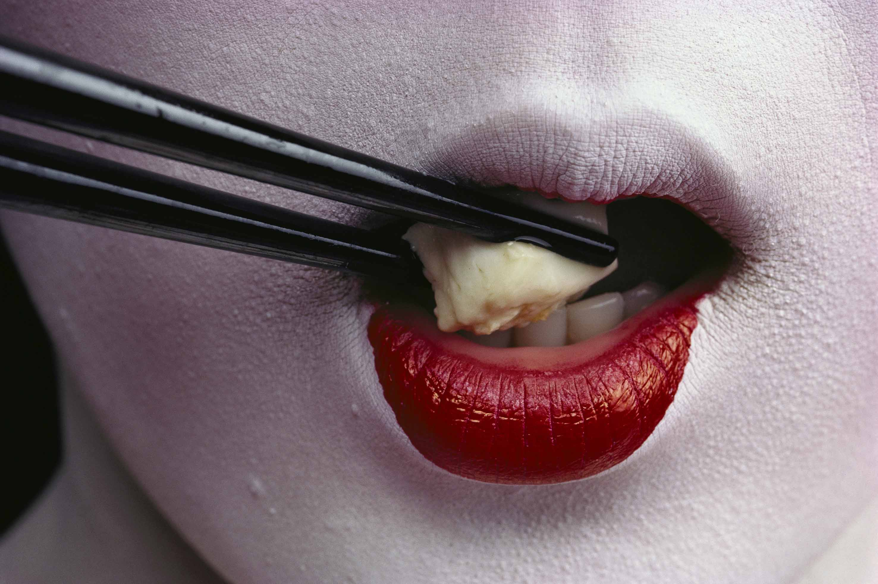 Close view of a geisha eating tofu with chopsticks.