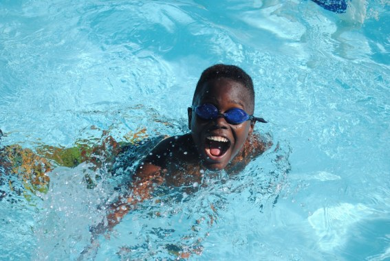 boy with wide smile and goggles swimming