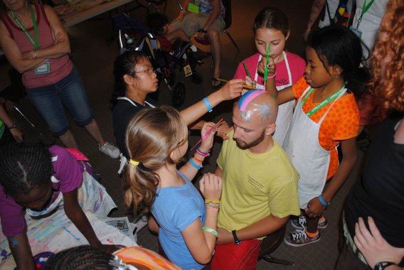 bald man allowing campers to paint head