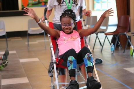 girl smiles as she dances in wheelchair