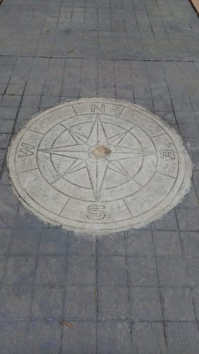 concrete compass embedded in cobblestone sidewalk