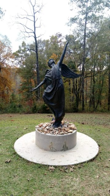 iron statue of angel with right hand uplifted towards the sky