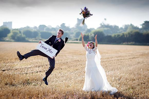 Photograph of bride and groom in field - country wedding with thank you sign