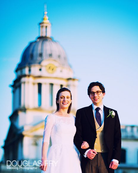 Bride and Groom with Old Royal NAval Collage behind them, with beautiful blue sky.