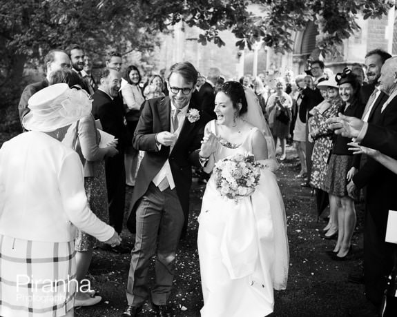 bride and groom with confetti outside Herefordshire church
