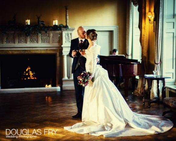 Bride and groom in front of fire at Hampton Court House
