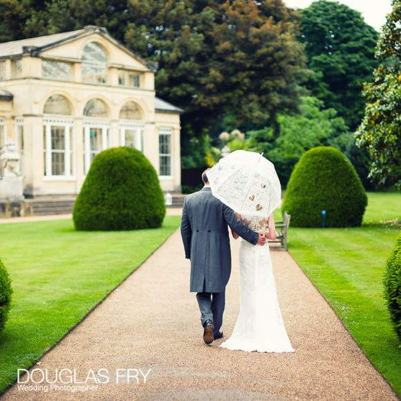 Couple walking through Syon Park on wedding day
