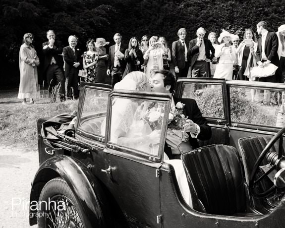 Bride and groom leaving the guests for the reception in vintage car