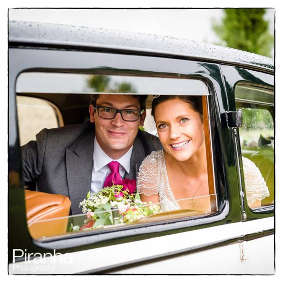Bride and groom in car leaving Worth Abbey after wedding ceremony