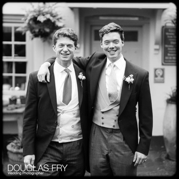 Groom and bestman in black and white in front of pub before wedding
