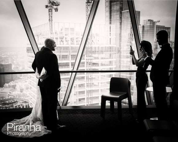 Bride and groom photographed by guests at the Gherkin
