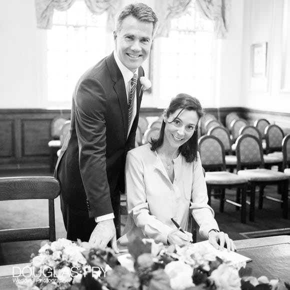 Black and white photograph of couple signing register in Oxford Register Office