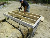 Applying construction cement to the coop floor joists