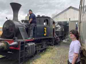 Two steam locomotives are parked outside the locomotive shed. A volunteer is on top of one of them making adjustments to valves. A second volunteer watches from the ground, wearing a white T shirt that is very grubby.