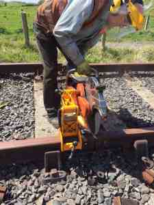 A volunteer wearing face and eye protection operates a large petrol driving circular saw to cut a section off the end of a length of rail.