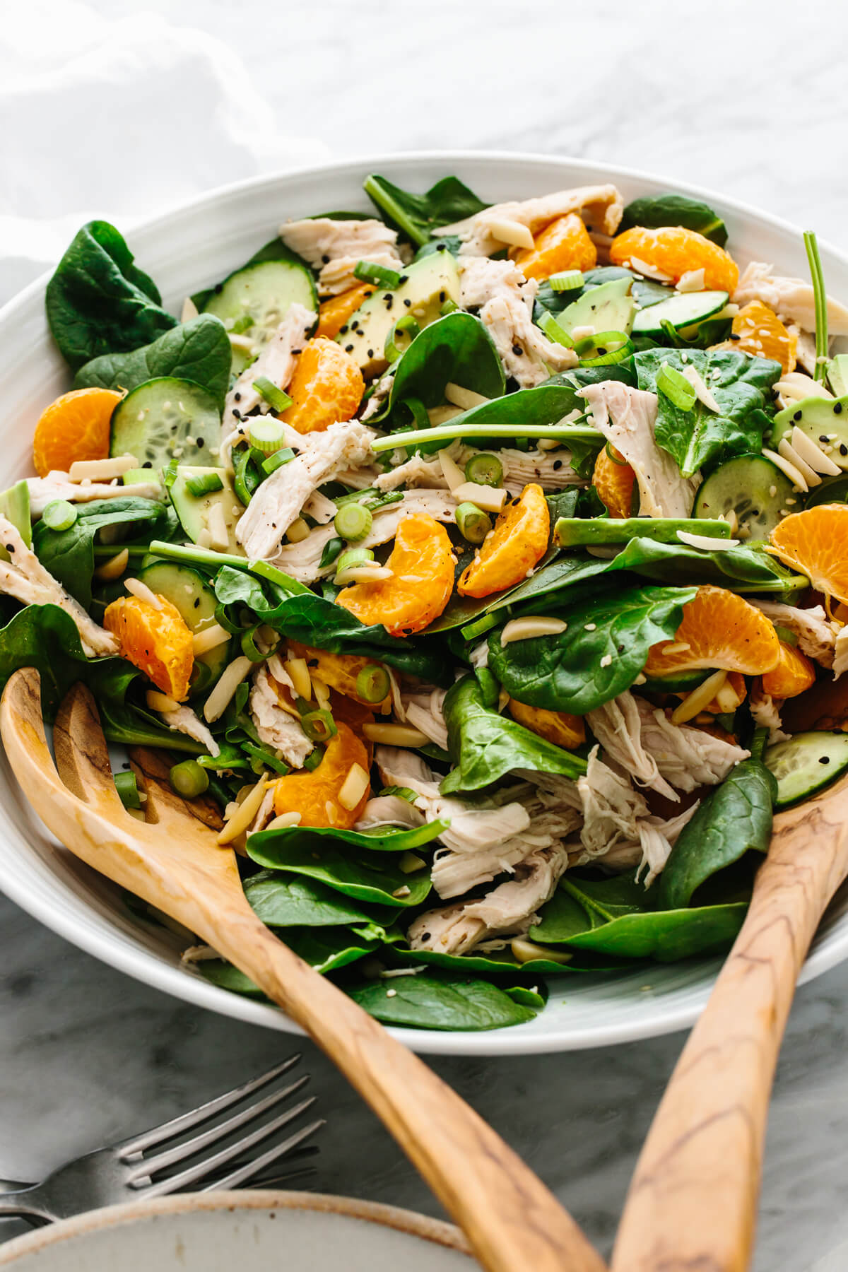Mandarin chicken salad in a bowl with serving spoons.