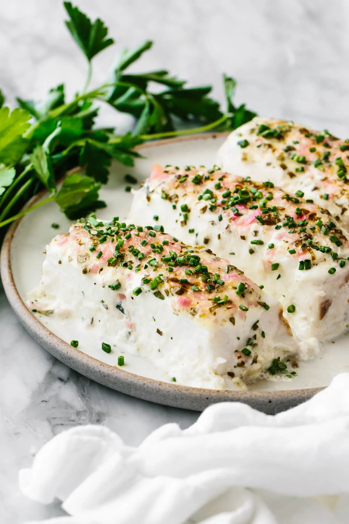 Baked halibut with herbed mayonnaise crust on a plate.