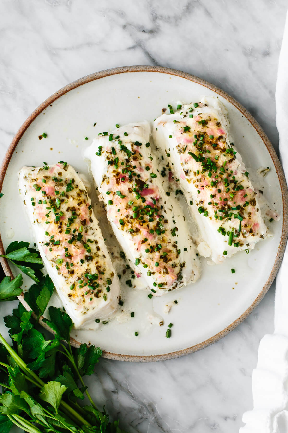 Baked halibut fillets on a plate next to cilantro