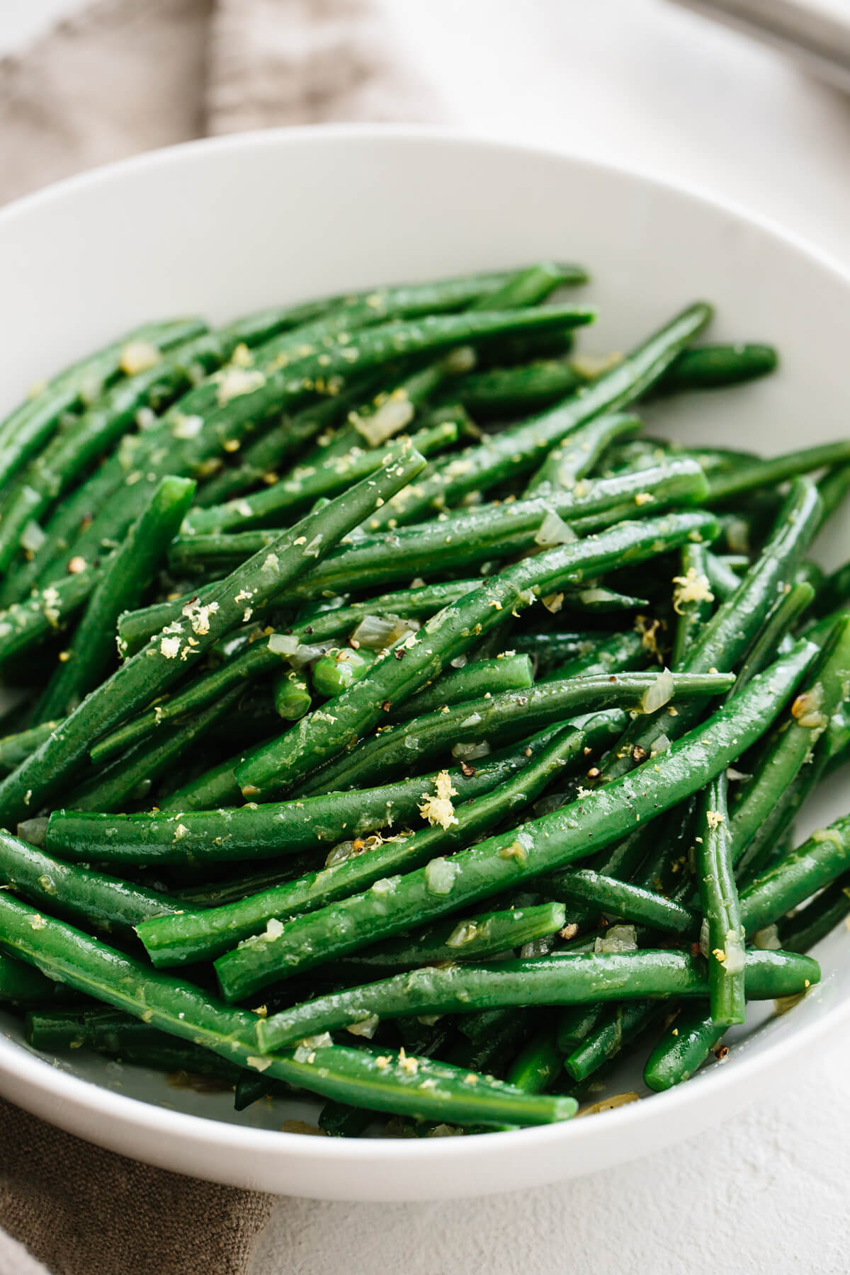 Green beans garnished with shallots and lemon in a white bowl.