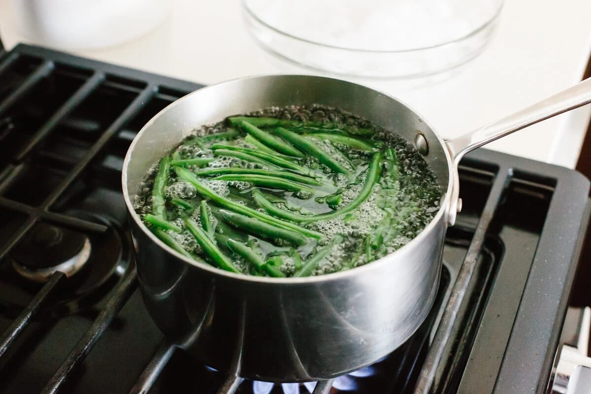Blanching and boiling green beans on the stove.