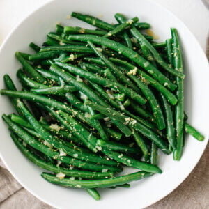 Green beans topped with lemon in a white bowl.