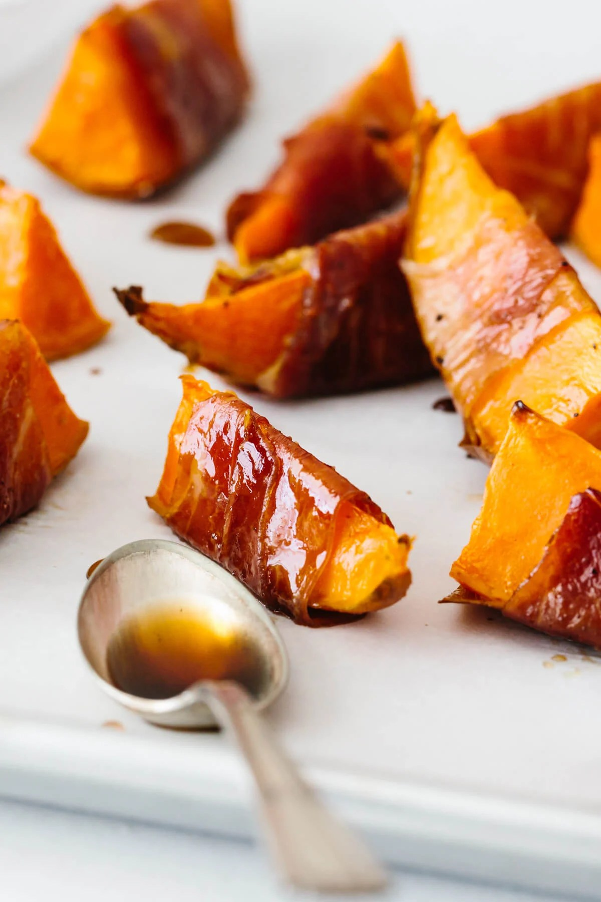 A single piece of sweet potato wrapped in prosciutto and baked.