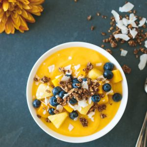 (gluten-free) Mango Smoothie Bowl. The perfect summer smoothie bowl, filled with mangoes, pineapple, blueberries and gluten-free granola.