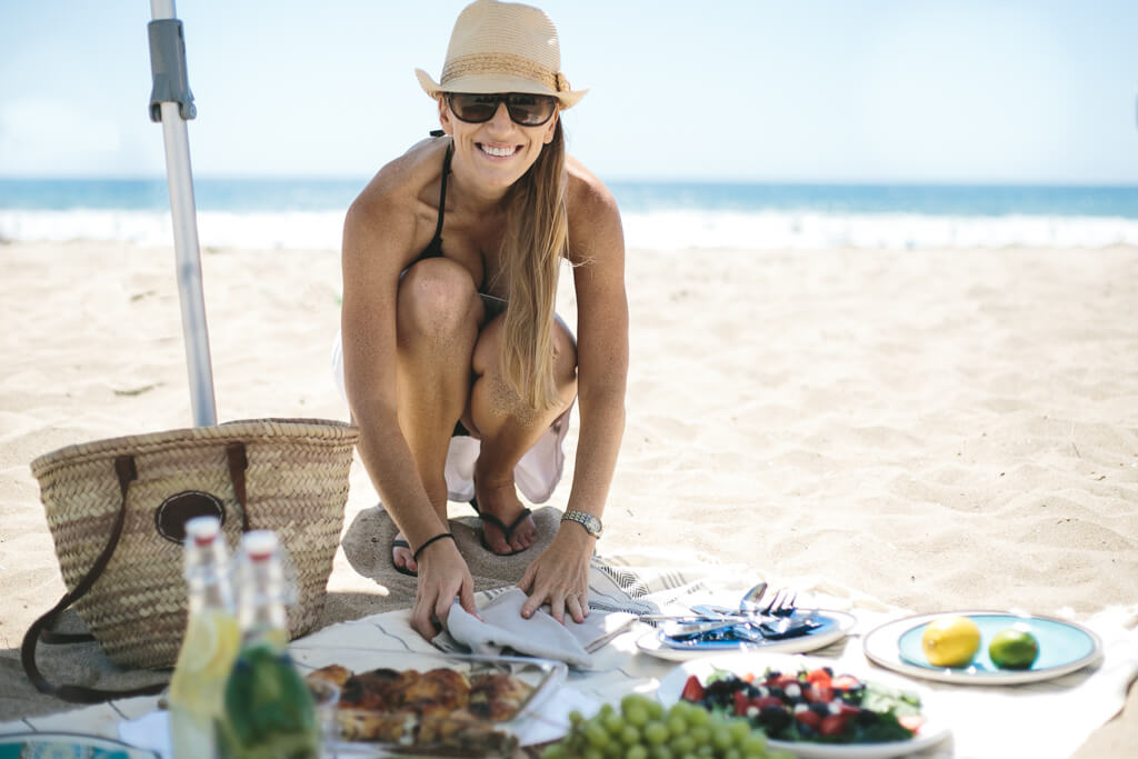 Girl setting up labor day picnic on the beach.