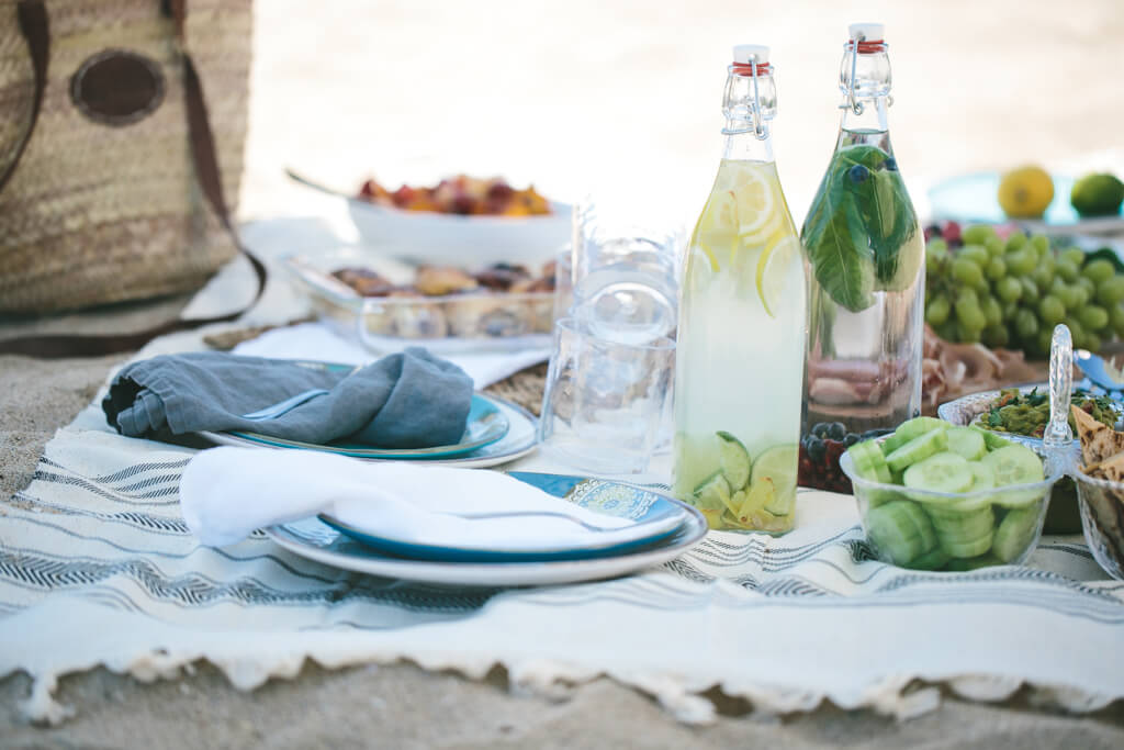 Beach picnic on a towel with bottles of infused water.