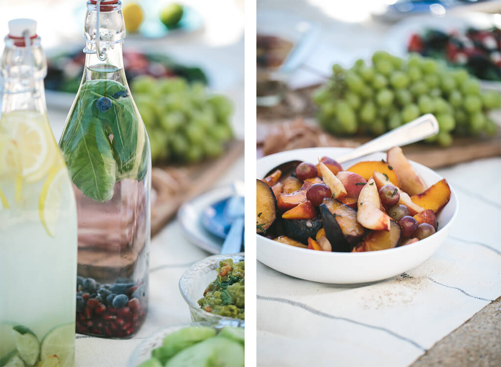 Two bottles of infused water and a beach blanket of picnic food.