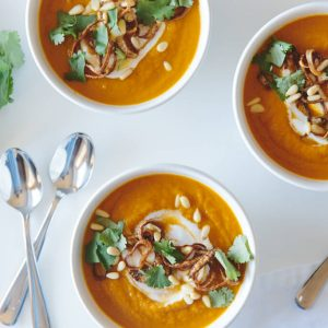 Carrot ginger soup with crispy shallots and coconut cream. A healthy soup that's gluten-free and dairy-free.