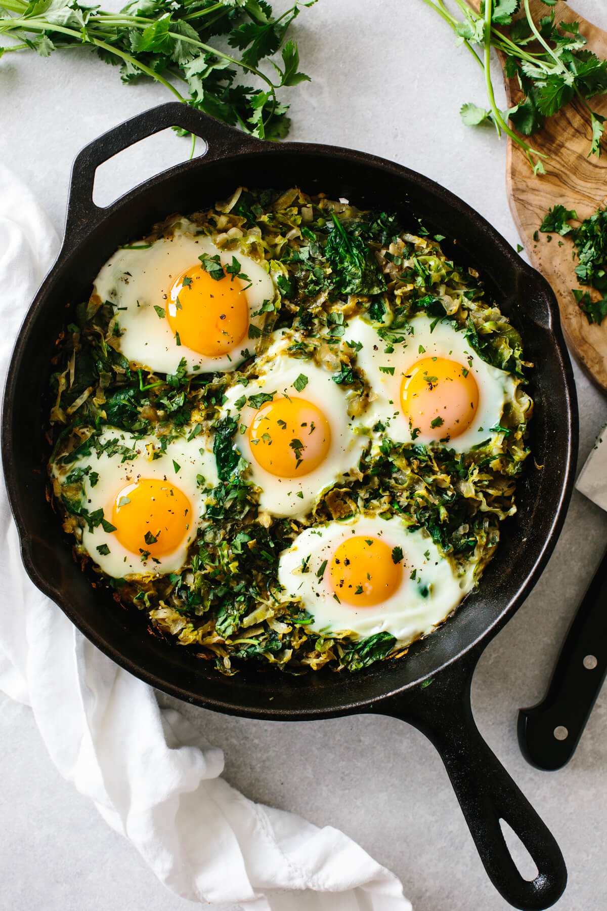 A cast iron pan filled with green shakshuka.