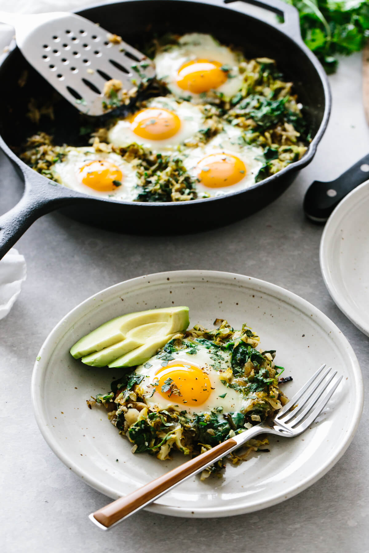 Scooping out a portion of green shakshuka to a plate, topped with avocado.