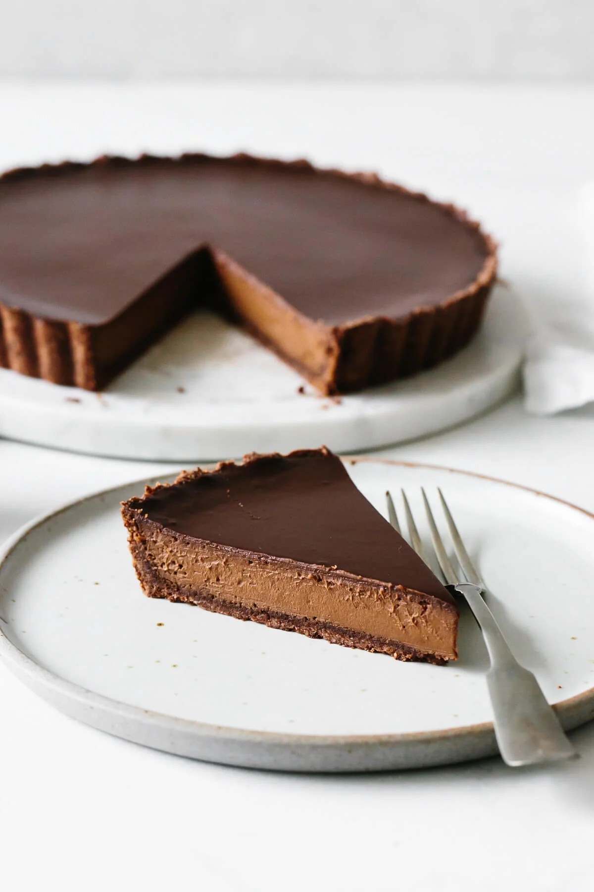 A single slice of chocolate tart on a plate.