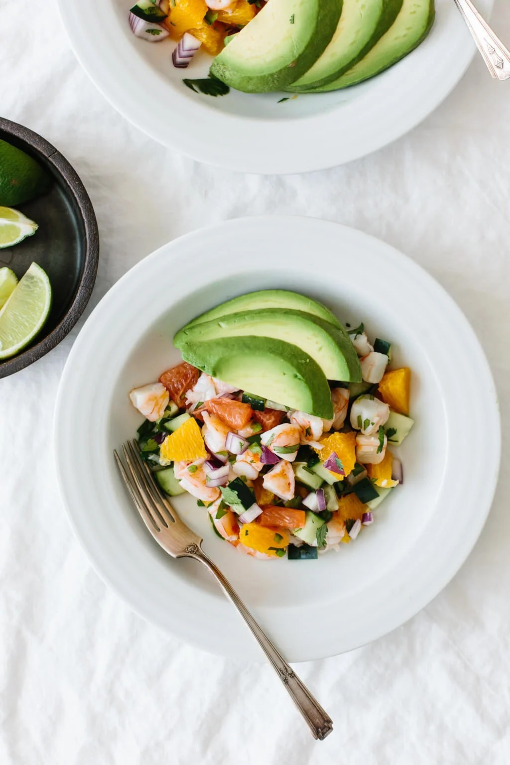 Shrimp ceviche in a white bowl and topped with avocado.
