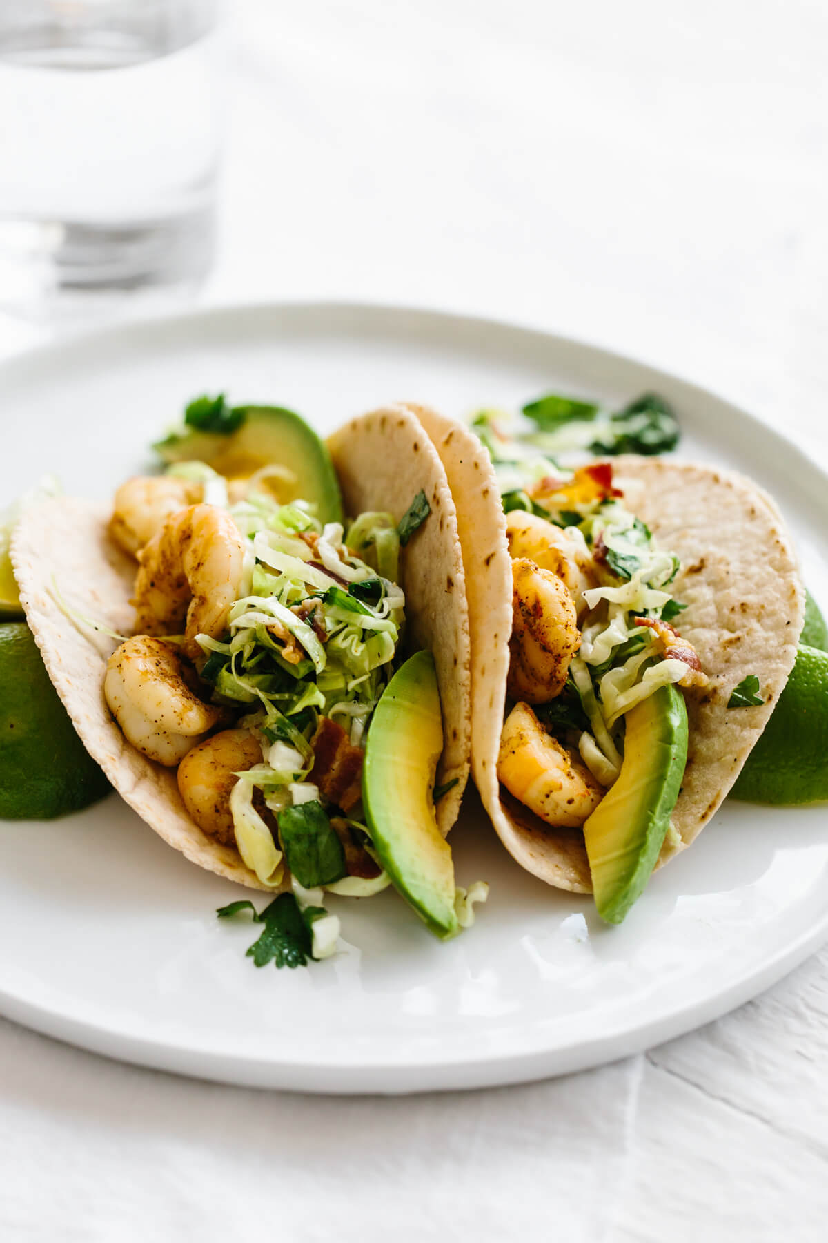 Shrimp tacos on a plate with avocado.